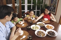 Family of four eating at home - Asia Images Group