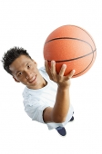Young man holding basketball, looking up at camera - Asia Images Group
