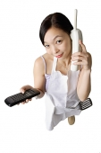Woman in apron using cordless phone, holding remote control - Asia Images Group