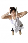 Woman in apron using cordless phone, frowning - Asia Images Group