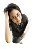 Young woman with glasses, carrying book, scratching hair - Asia Images Group