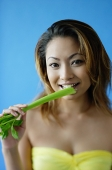 Woman looking at camera, eating celery - Asia Images Group