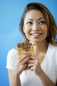 Woman holding bar of chocolate, smiling, looking away - Asia Images Group