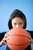 Woman wearing hooded shirt, holding basketball over face - Asia Images Group