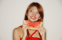 Woman with a slice of watermelon, smiling - Asia Images Group