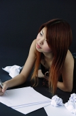 Woman lying down with pen and paper, looking away - Asia Images Group