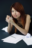 Woman holding crumpled paper in hands, looking at camera - Asia Images Group