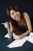 Woman holding crumpled paper and pen, smiling at camera - Asia Images Group