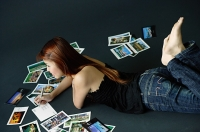 Woman lying on floor, writing on backs of postcards - Asia Images Group