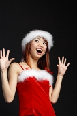 Woman wearing Santa hat and red dress, mouth open in surprise - Asia Images Group