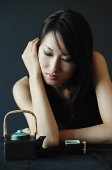 Woman with eyes closed, teacup and teapot next to her - Asia Images Group