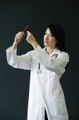 Female doctor standing, looking at syringe - Asia Images Group