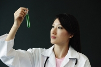Doctor looking at test tube - Asia Images Group