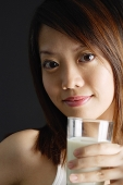 Young woman holding glass of milk, looking at camera - Asia Images Group