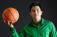 Young man wearing green tracksuit jacket, holding basketball - Asia Images Group