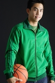 Young man wearing green tracksuit jacket, holding basketball, looking at camera - Asia Images Group