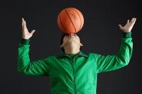 Young man balancing basketball on nose - Asia Images Group