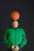 Young man in green jacket balancing basketball on nose - Asia Images Group