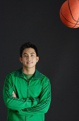 Young man in green jacket, arms crossed, basketball in the air - Asia Images Group