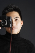 Young man dressed in black looking through camera - Asia Images Group