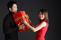 Young man giving gift to woman, woman turning to smile at camera - Asia Images Group