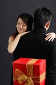 Man holding gift behind his back, woman embracing him - Asia Images Group
