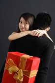 Man holding gift behind his back, woman embracing him, looking over shoulder at camera - Asia Images Group