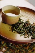 Tea cup on tray, tea leaves scattered around - Asia Images Group