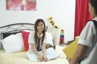 Girl in school uniform sitting on bed, smiling at person in foreground - Asia Images Group