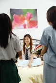 Girl in school uniform sitting on bed, two other girls facing her - Asia Images Group