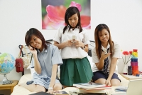 Girls in school uniform sitting on bed, using mobile phones - Asia Images Group