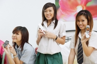 Girls in school uniform, sitting on bed, holding mobile phones - Asia Images Group
