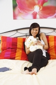 Girl sitting on bed, hugging stuffed toy, using mobile phone, smiling at camera - Asia Images Group