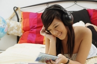 Girl lying on bed, holding CD case, listening to headphones - Asia Images Group