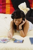 Girl lying on bed, listening to headphones - Asia Images Group