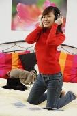 Girl in bedroom, kneeling on bed, listening to headphones - Asia Images Group