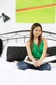 Girl in bedroom, sitting on bed, looking at camera - Asia Images Group