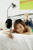 Girl in bedroom, lying on bed, holding mobile phone, looking at camera - Asia Images Group