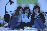 Three girls in bedroom, watching TV and eating popcorn - Asia Images Group