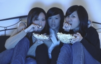 Three girls in bedroom, eating popcorn, watching TV - Asia Images Group