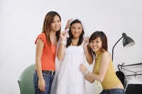 Young woman in white dress and veil, surrounded by two friends - Asia Images Group