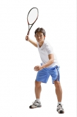 Young man holding tennis racket, waiting - Asia Images Group