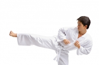 Young man in martial arts uniform, kicking - Asia Images Group