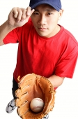 Young man holding baseball glove and ball, adjusting cap - Asia Images Group