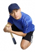 Young man crouching, holding baseball bat - Asia Images Group
