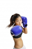 Young woman wearing boxing gloves, looking at camera - Asia Images Group