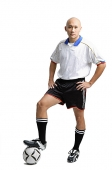 Young man wearing soccer uniform, standing with one leg on ball - Asia Images Group