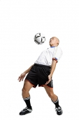 Young man in soccer uniform, hitting ball with his chest - Asia Images Group