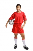 Young woman in soccer uniform, carrying soccer ball under arm - Asia Images Group