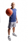 Young man standing, holding basketball - Asia Images Group